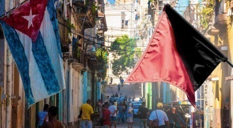 Cuban and anachist flags hang over a street